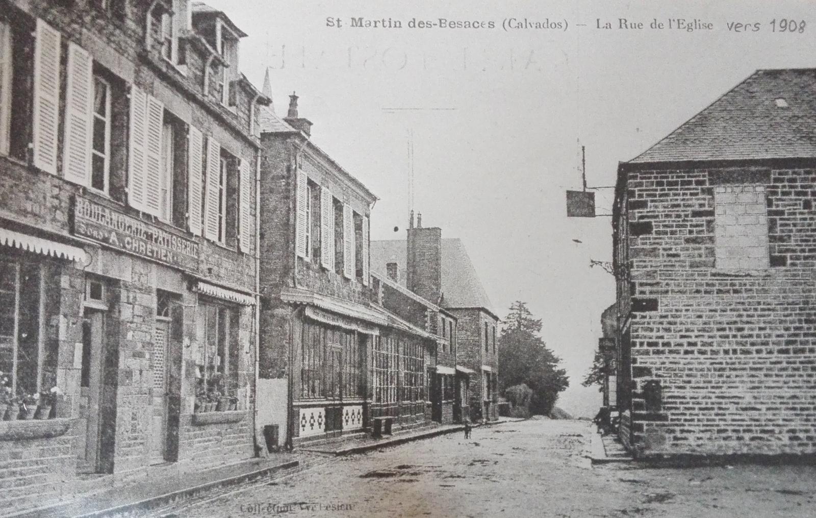 Saint-Martin-des-Besaces - rue de l'église vers 1908, l' église se trouve en retrait sur la gauche, on distingue juste le haut du clocher au niveau des toits de maison, au premier plan la boulangerie-pâtisserie A CHRETIEN