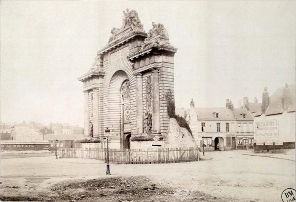 Lille -  La porte de Paris est l'édifice d'enceinte le plus célèbre de Lille. Elle est pourtant méconnue et mal datée, en raison des nombreux remaniements qu'elle a connus depuis l'origine de sa construction. En réalité, il existait déjà une porte d'enceinte dès le XIIIe siècle nommée porte des Malades, car elle menait au faubourg du même nom, connu pour sa léproserie. La porte avait été construite suite au IIe agrandissement vers 1273 qui entraîna l'annexion des paroisses de Saint-Maurice et de Saint-Sauveur dans le nouveau périmètre fortifié. En 1677¹, la vieille porte des Malades devient la porte de Paris. Ce n'est qu'en 1684¹ que la porte est remaniée et nous doit son aspect actuel. Confiés à Simon Vollant, les travaux transforment alors la vieille porte en une véritable entrée triomphale dont le style architectural est très représentatif du bon goût français sous Louis XIV. Restaurée à la fin du XIXe siècle, après une sauvegarde assez miraculeuse, la porte de Paris a retrouvé sa superbe suite à une ultime restauration en 2002.Sur ce cliché, la Porte de Paris semble être en pleine campagne. Elle n'a pas encore été restaurée et n'a pas la splendeur actuelle.