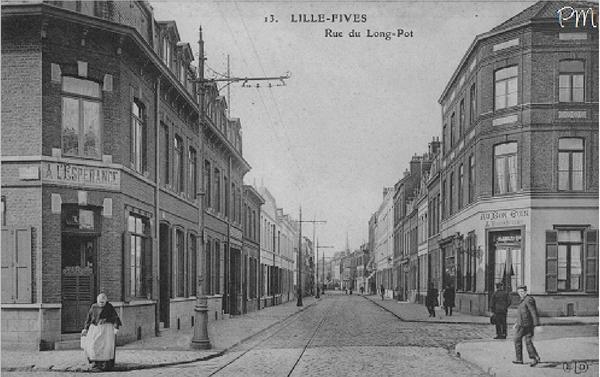 """Lille -  La rue du Long-Pot se poursuit ici en direction de la rue Pierre-Legrand, à l'intersection avec la rue Parmentier (sur la gauche) et l'ancienne rue des Processions, actuelle rue Francisco Ferrer depuis 1926¹ (sur la droite). On distingue, dans le fond, la flèche de l'église Notre-Dame. L'actuel carrefour avec ces trois rues est reconnaissable aujourd'hui. Le bar faisant l'angle avec la rue Ferrer est aujourd'hui dénommé """"Au Stade"""" et se situe toujours au n°79, rue du Long-Pot. C'est surtout le tronçon précédant ce carrefour qui a été fortement transformé depuis l'implantation du stade Ballet et de la piscine de Fives.lilledantan.com"""